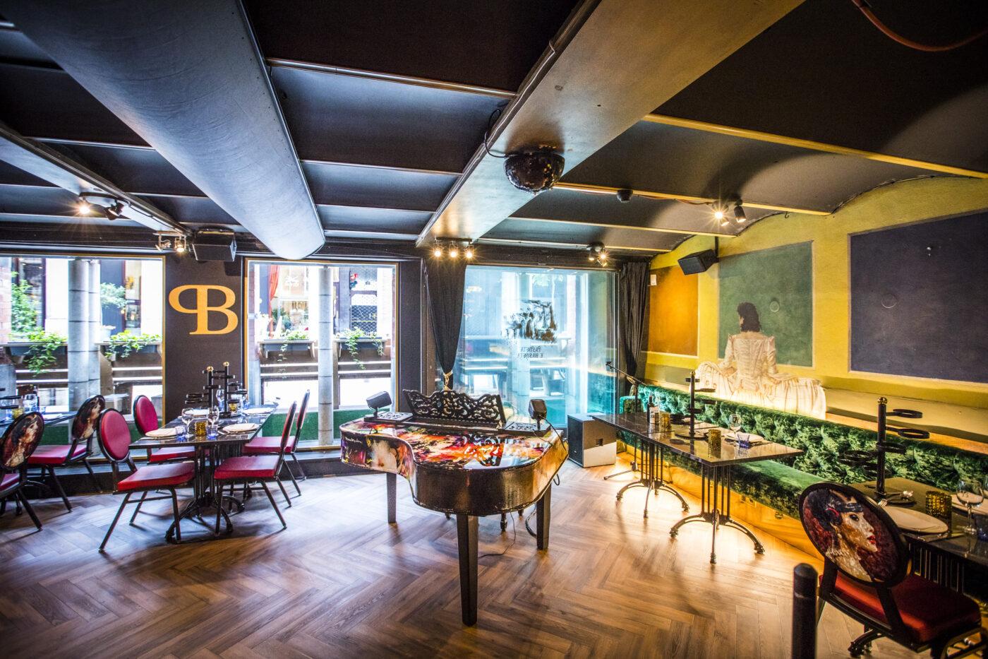 Restaurant met piano en donkere visgraat vloer in Amsterdam