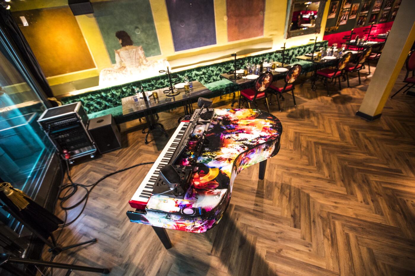 Bovenaanzicht van restaurant met piano en donkere visgraat vloer in Amsterdam