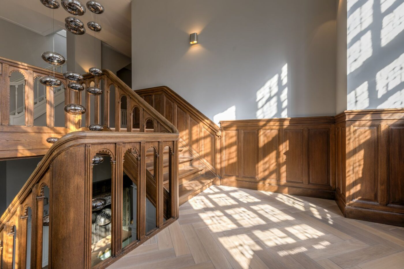 Donkere houten visgraat vloer in de trapgang in Bussum