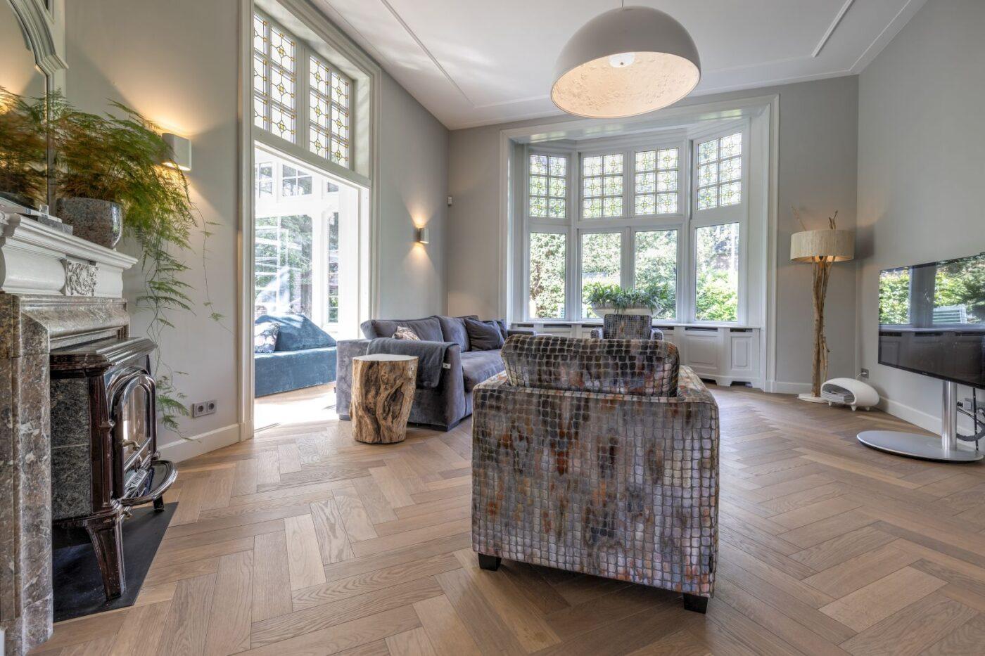 Donkere houten visgraat vloer in de woonkamer in Bussum